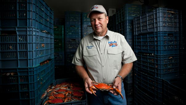 Man holding a blue crab.